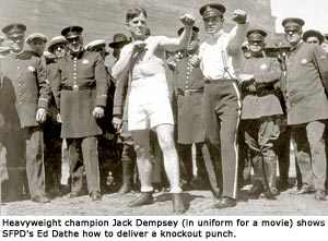 Jack Dempsey shows SFPD's Ed Dathe how to deliver a knockout punch